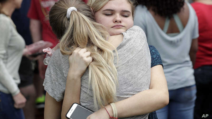 Students hug outside a staging area at the First Baptist Church of Ocala as parents arrive to pick them up after a shooting incident at nearby Forest High School in Ocala, Florida, April 20, 2018.