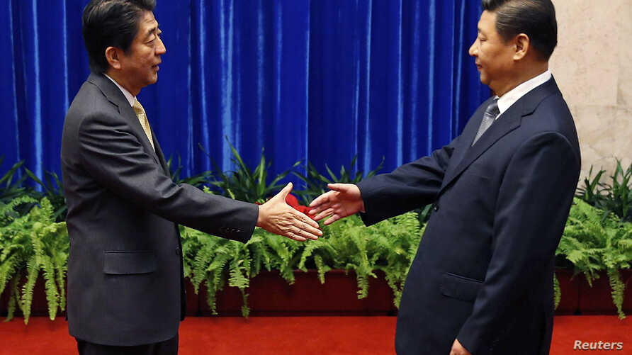 Japan's Prime Minister Shinzo Abe shakes hands with China's President Xi Jinping (R) during their meeting at the Great Hall of the People, on the sidelines of the Asia Pacific Economic Cooperation (APEC) meetings, in Beijing, Nov. 10, 2014.