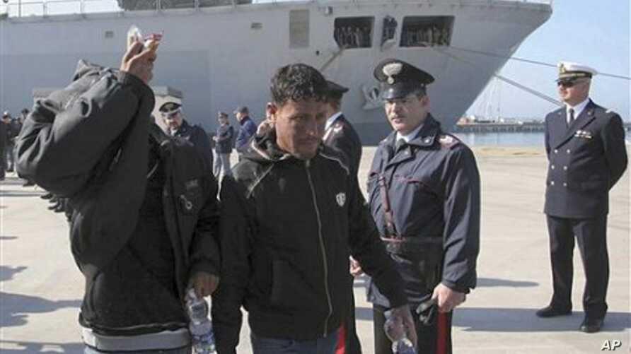 Migrants disembark from the Italian Navy vessel San Marco as they arrive at the harbour in Taranto , southern Italy, March 27, 2011