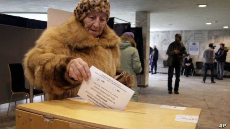 A Latvian woman casts her ballot paper at a polling station during a language referendum in Riga, Latvia, February 18, 2012.