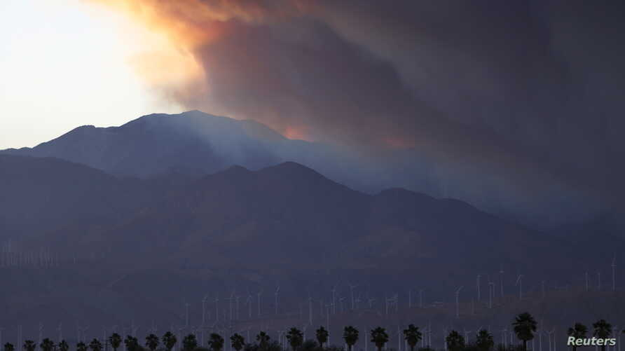 A smoke plume from the Lake Fire in the San Bernardino National Forest is seen at sunset, rising over the Coachella Valley from Palm Springs, California, June 18, 2015.