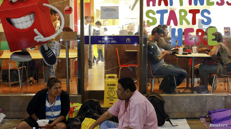 Anti-government protesters eat dinner outside a McDonald's restaurant in central Bangkok, February 6, 2014.