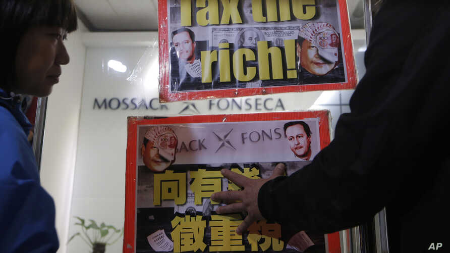FILE - Placards featuring portraits of Chinese President Xi Jinping and demanding taxes on the rich are displayed near the regional head office of Panama-based law firm Mossack Fonseca in Hong Kong, April 12, 2016. The Panama Papers have shown Chines