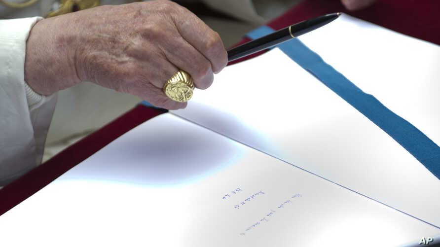 FILE - Pope Benedict XVI signs a book during a visit to the Ardeatine Caves Memorial in Rome, March 27, 2011.