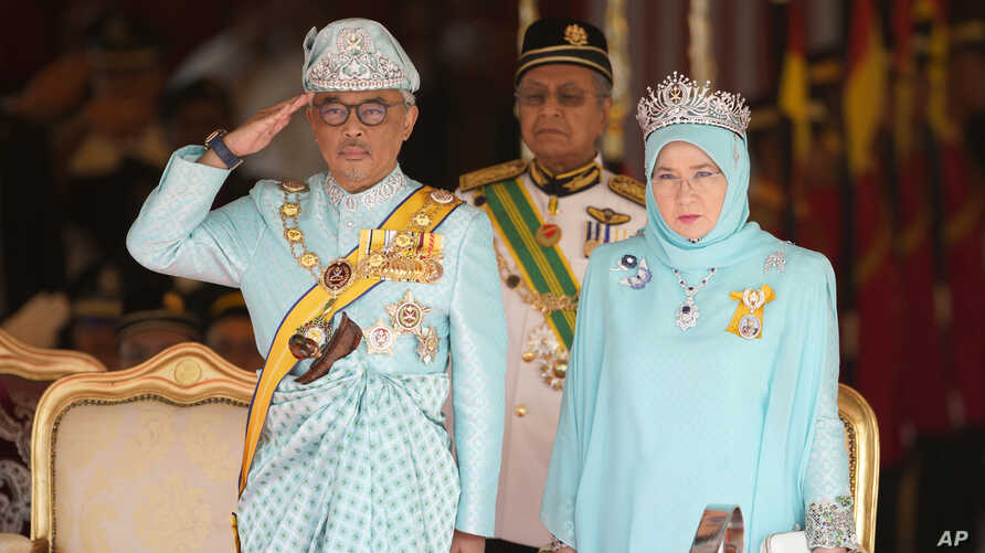 Malaysia's King Sultan Abdullah Sultan Ahmad Shah salutes next to Queen Tunku Azizah Aminah Maimunah and Prime Minister Mahathir Mohamad, center, during his welcome ceremony at Parliament House in Kuala Lumpur, Jan. 31, 2019.