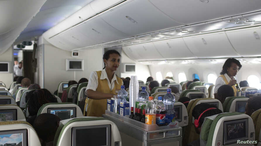 Female crew members serve lunch on board an Ethiopian Airlines flight from Addis Ababa Nairobi, April 27, 2013.