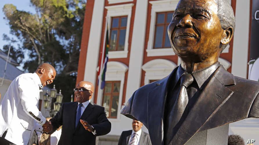South African President Jacob Zuma (second l) talks with Mandla Mandela (l) after they and other dignitaries unveiled a bust of former South African President Nelson Mandela (r) at the South African Parliament in Cape Town, South Africa, April 28, 20