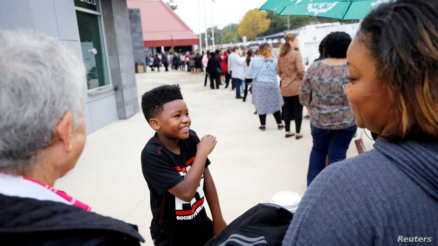 Masada Hart, 9, waits in line with his mother before Oprah Winfrey takes part in a town hall meeting with Democratic gubernatorial candidate Stacey Abrams ahead of the mid-term election in Marietta, Georgia, U.S., Nov. 1, 2018.