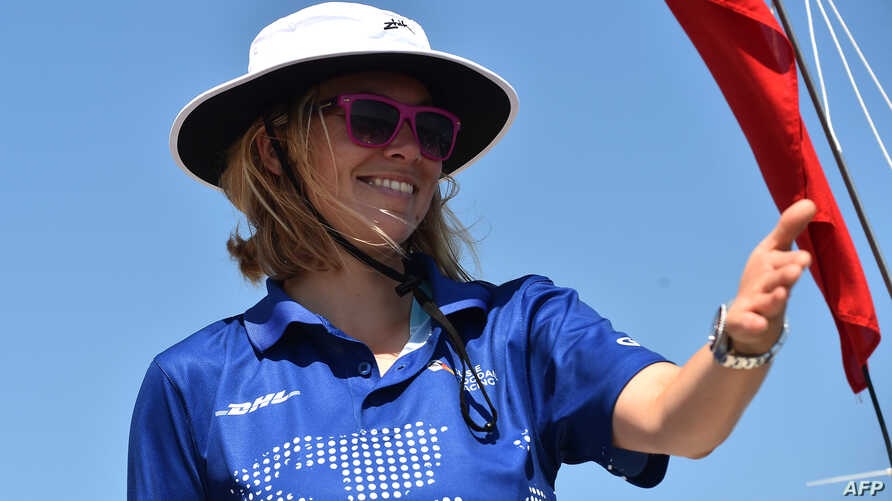 """FILE - Britain's Susie Goodall gestures on her boat """"DHL Starlight"""" as she sets sail from Les Sables-d'Olonne, France, July 1, 2018, at the start of the solo around-the-world """"Golden Globe Race."""""""