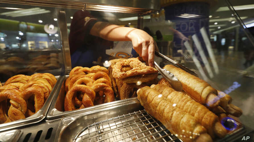 FILE - A worker sells a Pretzel Dog at an Auntie Anne's in Kuala Lumpur, Malaysia. The chain has been told by Islamic authorities that its popular Pretzel Dog, which contains no dog meat, has to be renamed because it is confusing for Muslim consumer