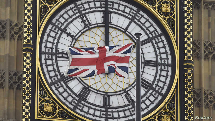 A British Union flag flutters in front of one of the clock faces of the 'Big Ben' clocktower of The Houses of Parliament in central London, Feb. 22 , 2016