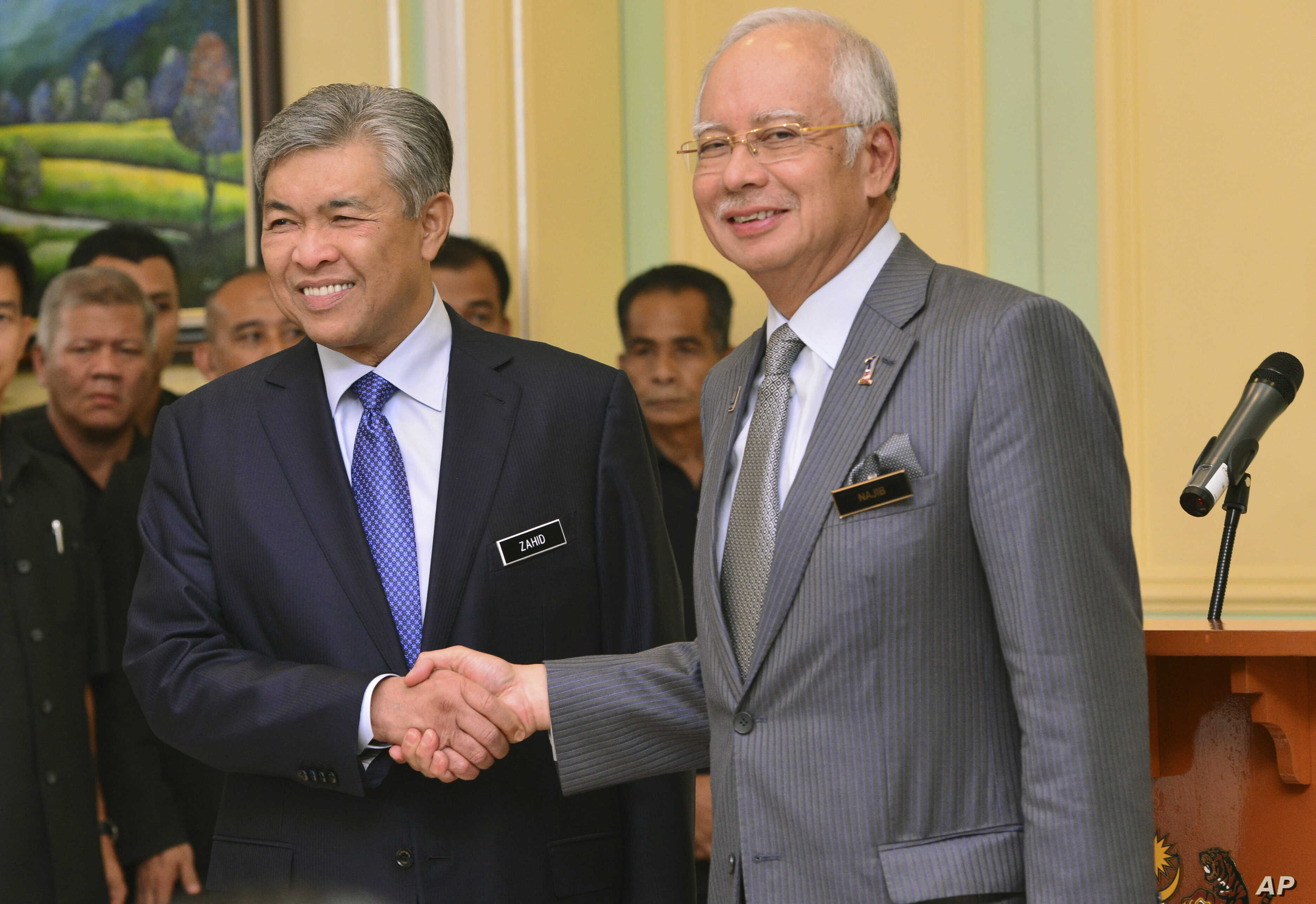 Malaysia's Prime Minister Najib Razak, right, shakes hands with his newly-appointed Deputy Prime Minister Ahmad Zahid Hamidi after addressing a press conference at the prime minister's office in Putrajaya, Malaysia, July, 28, 2015.
