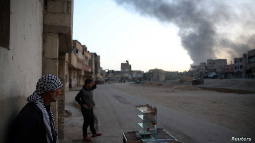 Syrian residents watch as smoke rises from Harasta area, as seen from Douma, in the eastern Damascus suburb of Ghouta, Syria Nov. 14, 2017. On Thursday, Syrian war monitors said Russian jets killed at least 20 civilians in rebel-held areas near the
