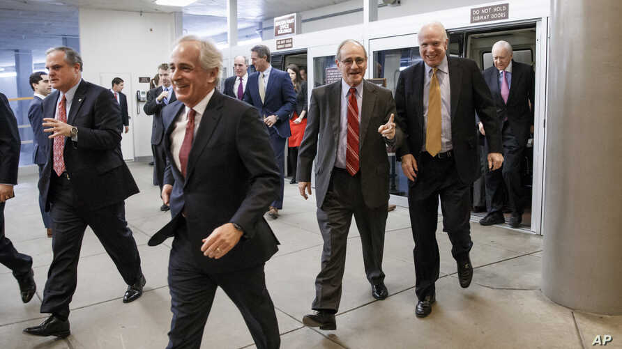 From left, Sens. Mark Pryor, D-Ark., Bob Corker, R-Tenn., James Risch, R-Idaho, John McCain, R-Ariz., and Orrin G. Hatch, R-Utah, rush to the Senate floor for a procedural vote to advance a defense spending bill, ahead of a midnight deadline to keep