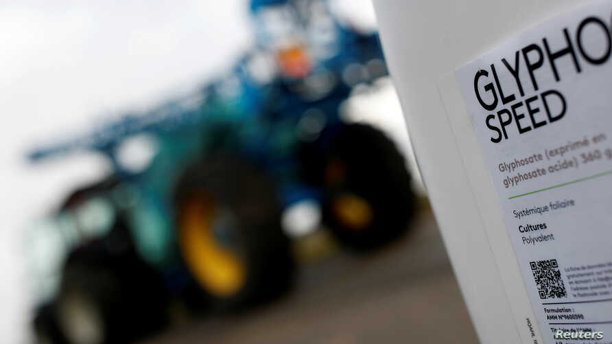 FILE - A can of glyphosate weedkiller is seen in front of a tractor with a pulverizer system as French farmer Herve Fouassier is interviewed by Reuters in Ouzouer-sous-Bellegarde, France, Nov. 30, 2017.