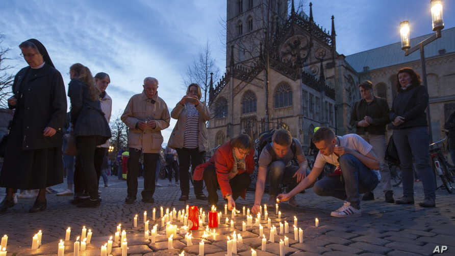 People light candles during a memorial service in front of the Muenster cathedral, in Muenster, Germany. April 8, 2018, one day after a man killed two people and injured 20 others by crashing into people outside a popular bar before killing himself.