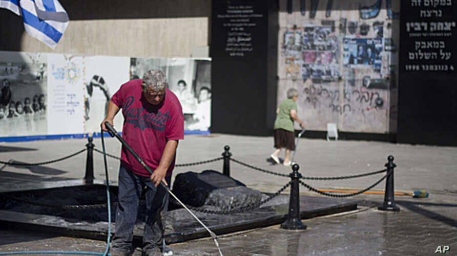 A worker cleans the vandalized memorial site of assassinated Prime Minister Yitzhak Rabin in Tel Aviv, early Friday, Oct. 14, 2011.
