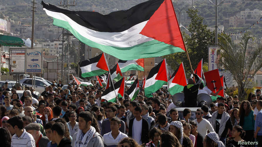 Israeli Arab demonstrators take part in a Land Day rally in the northern village of Araba, March 30, 2014.