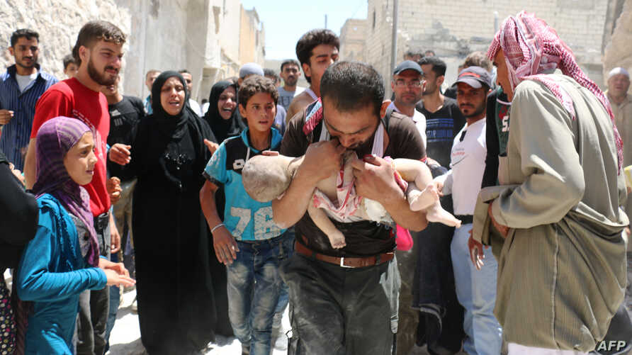 A Syrian man holds the body of his child after it was taken from under the rubble of destroyed buildings following a reported airstrike on the rebel-held neighborhood of al-Marjah in the northern city of Aleppo, July 24, 2016.
