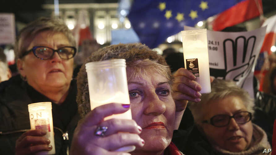 Poles protest plans by the ruling populist party for laws that would give it greater control over the courts and the national election commission, in Warsaw, Poland, Nov. 24, 2017. The evening demonstration came after lawmakers earlier in the day gav...