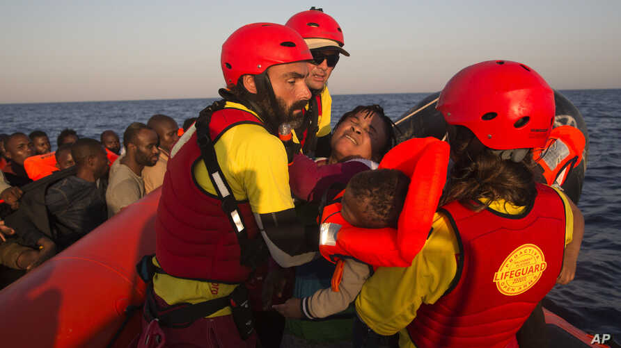 FILE - In this Aug. 20, 2016 file picture a woman from Nigeria and her baby are helped by members of Proactiva Open Arms NGO, before transferring them to an Italian navy ship, during a rescue operation at the Mediterranean sea, about 17 miles north o