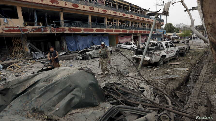 An Afghan policeman inspects the site of a blast near the Indian consulate in Jalalabad, Afghanistan, March 2, 2016. Suicide bombers targeted  the Indian consulate in the eastern city of Jalalabad.