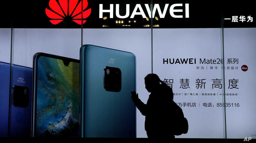 A woman browses her smartphone as she walks by a Huawei store at a shopping mall in Beijing, Dec. 11, 2018.