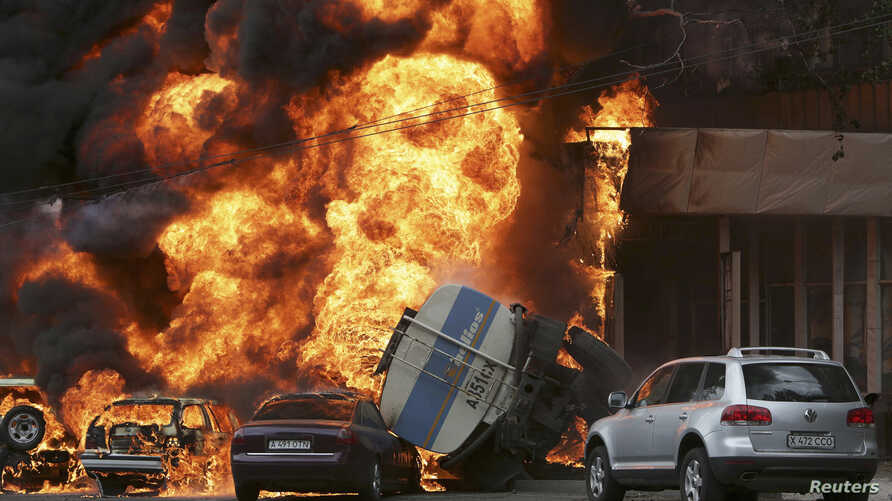 Burning vehicles are seen at the site of a fire in Almaty June 27, 2013. A 16-ton tanker rolled over after an accident and set ablaze parked cars and a nearby apartment building, Emergency Ministry reported. REUTERS/Sergey Khodanov (KAZAKHSTAN - Tags