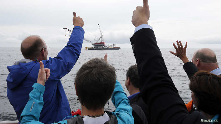 Elected officials and Deepwater Wind executives cheer during a ceremony to mark the installation of the first jacket support structure for a wind farm in the waters of the Atlantic Ocean off Block Island, Rhode Island, July 27, 2015.