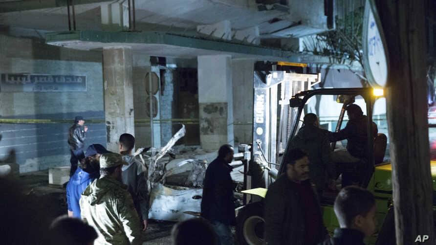 Security officers gather at the site of a car bombing near Italian Embassy in Tripoli, Libya, Jan. 21, 2017.
