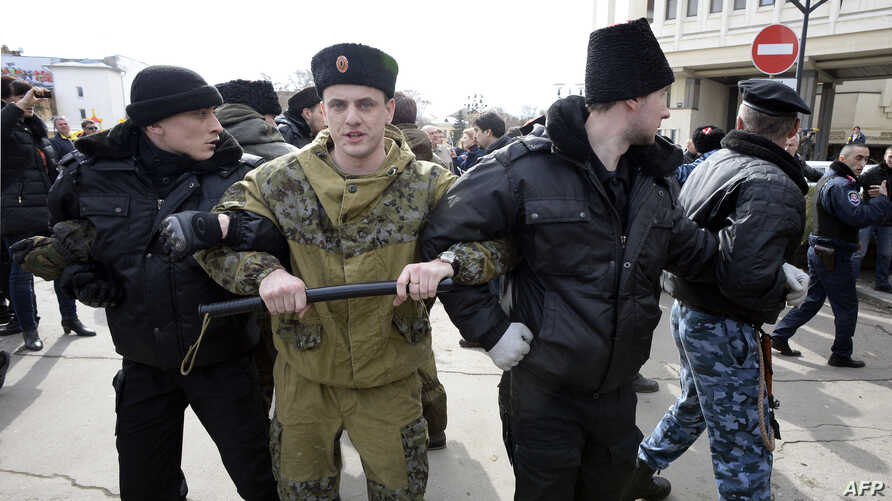 Pro-Russian volunteers stand guard in front of Crimea's parliament building during a pro-Russian rally in Simferopol, March 6, 2014.