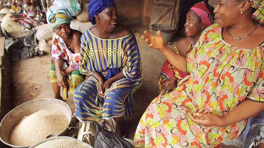 Women rice sellers chat in a busy market in Kindia, Guinea in this Aug. 21, 2002 photo.
