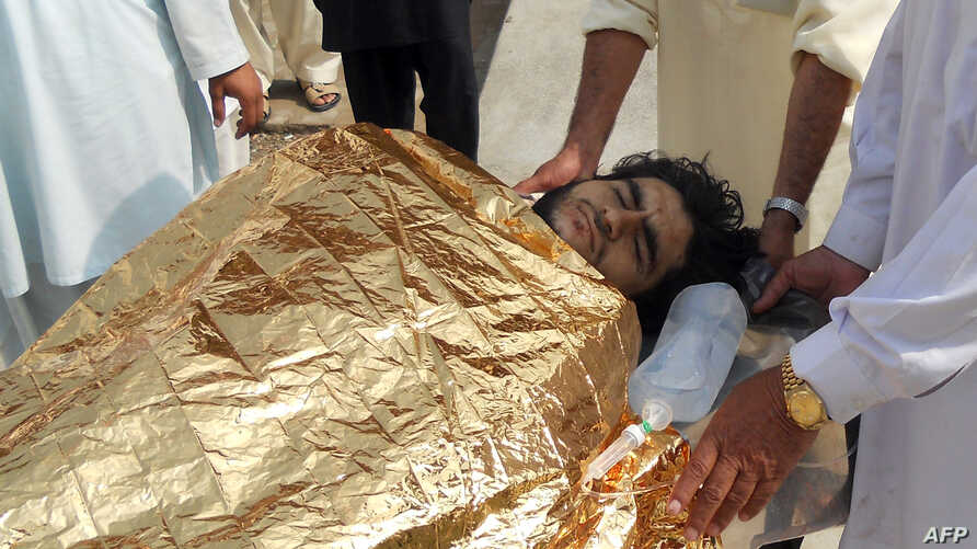 Pakistani men carry an injured bombing victim into a hospital in Kohat on October 3, 2013, following an attack on the home of militant commander Maulvi Nabi Hanfi by fighters from Tehreek-e-Taliban Pakistan (TTP) in Pakistan's Orakzai tribal district