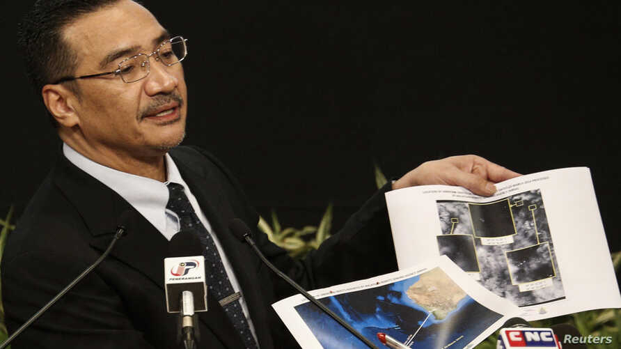 Malaysia's acting Transport Minister Hishammuddin Hussein holds satellite images as he speaks about the search for flight MH370, during a news conference at Putra World Trade Center in Kuala Lumpur, March 26, 2014.