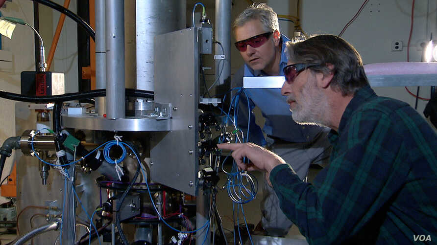 """NIST physicists Steve Jefferts (foreground) and Tom Heavner with the NIST-F2 """"cesium fountain"""" atomic clock, a new civilian time standard for the United States."""
