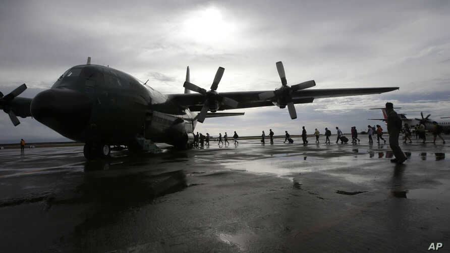 Typhoon survivors board a Philippine Air Force transport plane in Tacloban, Nov. 21, 2013.