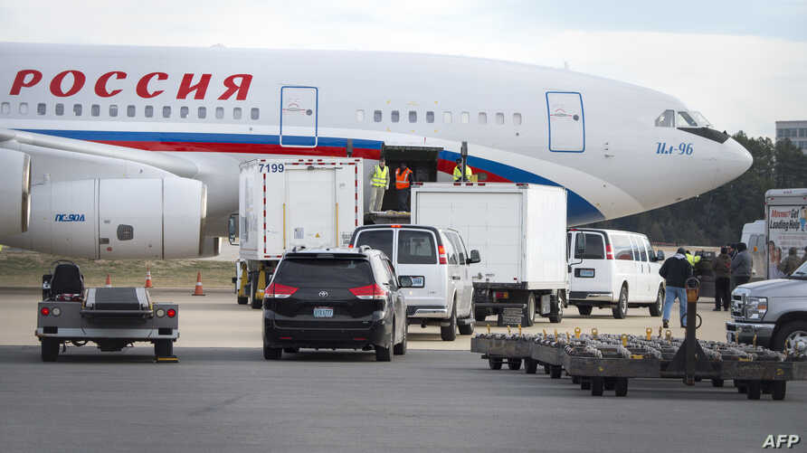 Vehicles pull up to a Russian aircraft to load freight at Dulles International Airport Dec. 31, 2016, in Sterling, Virginia, just outside Washington, D.C.