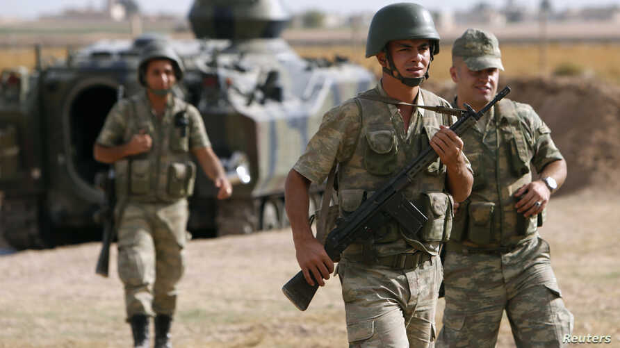 Turkish soldiers walk stand guard on the Turkish-Syrian border near the Akcakale border crossing, southern Sanliurfa province, October 5, 2012.