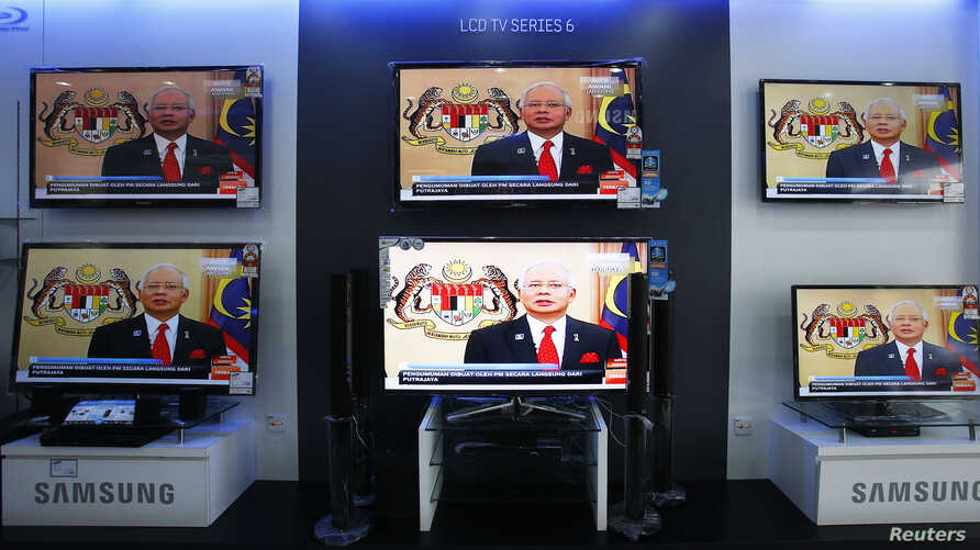 Malaysia's Prime Minister Najib Razak is seen on TV during a news bulletin as he announces the dissolution of parliament, at an electronics shop in Kuala Lumpur, April 3, 2013.