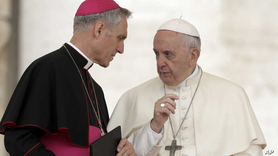 FILE - Pope Francis shares a word with Prefect of the Papal Household Georg Ganswein (L) during his weekly general audience, in St. Peter's Square, at the Vatican, May 2, 2018.