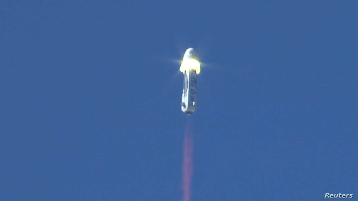 The New Shepard booster rocket, owned by Jeff Bezos' space company, Blue Origin, is shown at the moment of separation during the escape module testing in Culberson County, Texas, Oct. 5, 2016.