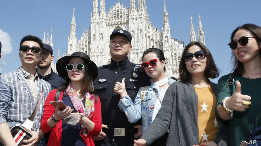 FILE - Chinese Police office poses with Chinese tourists in Milan's Duomo square, Italy, May 3, 2016.