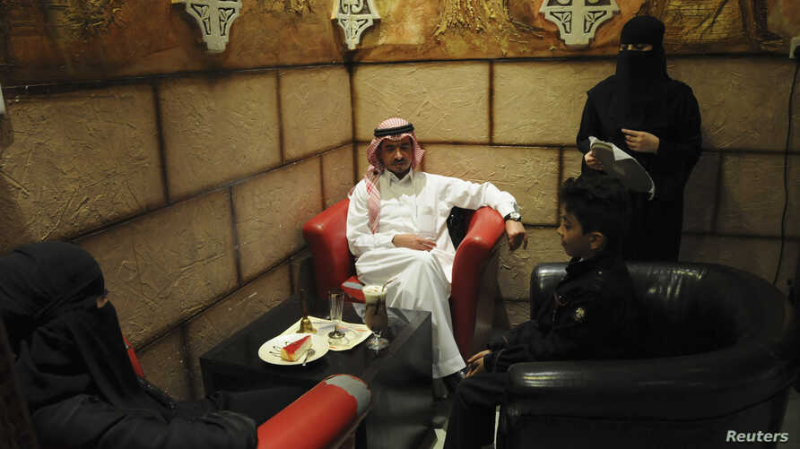 FILE - A veiled Saudi waitress (R) speaks to visitors at a coffee shop in Tabuk, 1,500 kilometers from Riyadh.