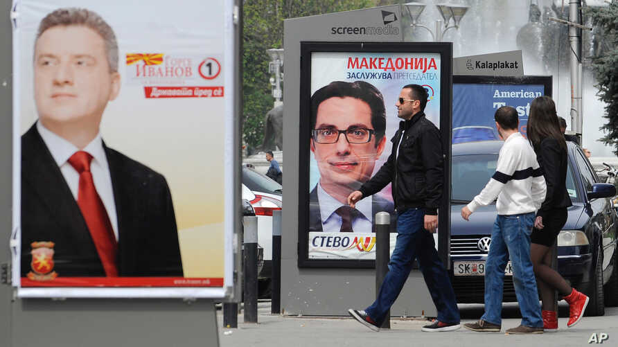 "Young people pass beside boards with election posters of Gjorge Ivanov, left, current Macedonian President and a candidate of the ruling conservative VMRO-DPMNE party, with a slogan ""The State Before All"", and Stevo Pendarovski, center, a candidate o"