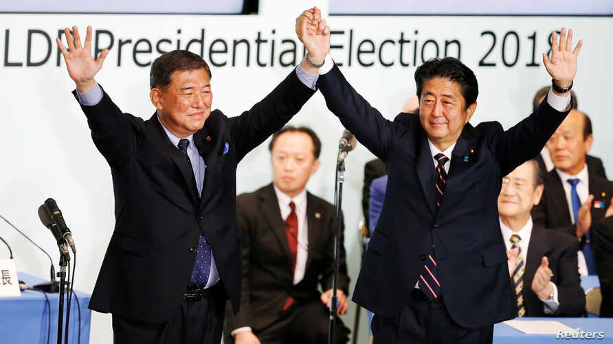 Japan's Prime Minister Shinzo Abe, right, who is also the ruling Liberal Democratic Party's leader, raises his hands with former defense minister Shigeru Ishiba after Abe won the ruling party leadership vote at the party's headquarters in Tokyo, Sept