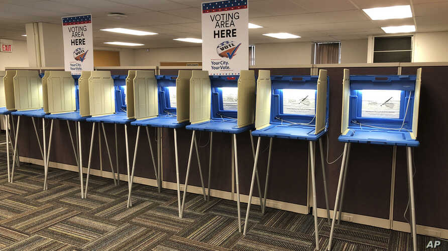 FILE - Voting booths stand ready in downtown Minneapolis for the opening of early voting in Minnesota, Sept. 20, 2018.