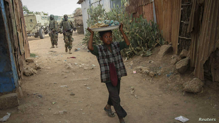A Somali boy carries a tray of nuts and snacks on top of his head as he walks near a market place in the town of Jawhar in Middle Shabelle region, north of the Somali capital Mogadishu, December 11, 2012.