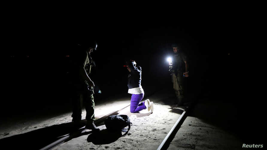 Migrant Yoniel Torres, 31, from Cuba is handcuffed after being detained by the police by a train line in a mined area of desert at the Chilean and Peruvian border in Arica, Chile, Nov. 14, 2018.