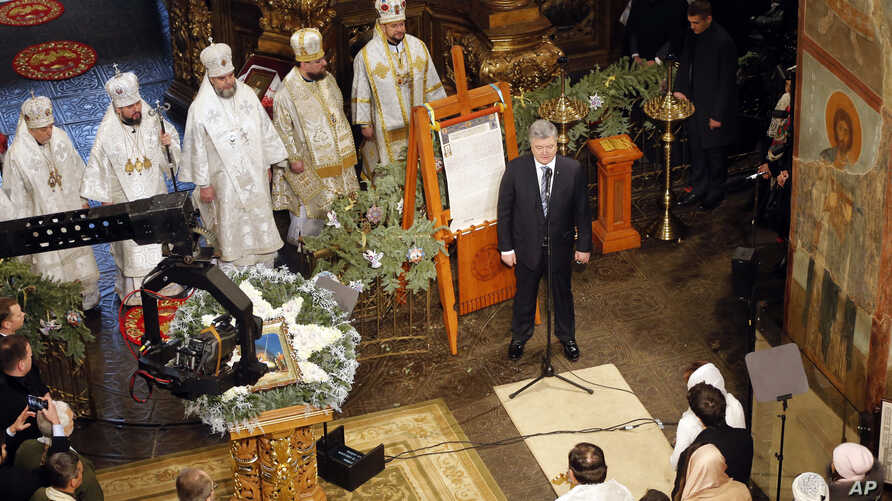 """Ukrainian President Petro Poroshenko delivers a speech standing next to the """"Tomos"""" decree of autocephaly for the Orthodox Church of Ukraine during the service marking Orthodox Christmas and celebrating the independence of the Ukrainian Orthodox Chur"""