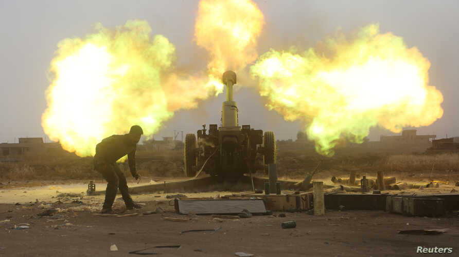 Popular Mobilization Forces (PMF) fire towards Islamic State militants during a battle on the outskirts of Al-Ba'aj, west of Mosul, May 26, 2017.
